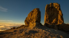 Roque Nublo monoliths on Gran Canaria at sunset overlooking Mount Teide on Tenerife above the clouds some 90km in the distance.