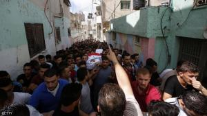 """Mourners carry the body of Palestinian Mohammed Abu Hashash, who was shot dead during clashes with Israeli forces the day before, during his funeral on August 17, 2016 in the al-Fawwar Palestinian refugee camp, south of the West Bank city of Hebron. The Palestinian health ministry said on August 16, 2016 that Mohammed Abu Hashash, 17, died after he was shot in the chest during clashes with Israeli forces conducting searches in the Fawwar camp. At least 25 other Palestinians were wounded in the clashes, Red Crescent medics said. The Israeli military did not confirm or deny casualties during the operation, which a spokeswoman said aimed to """"uncover weaponry"""" in the camp. / AFP / HAZEM BADER        (Photo credit should read HAZEM BADER/AFP/Getty Images)"""