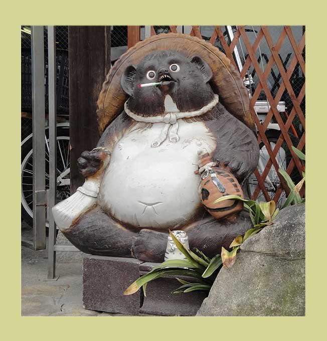 Dicke Tanukifigur mit Zigarette im Maul und Flasche in der Hand sitzt im Schneidersitz und sieht weggetreten aus