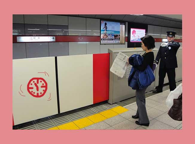 Tokioter U-Bahn-Gleis mit Passantin und Schaffner, der auf die Uhr blickt.
