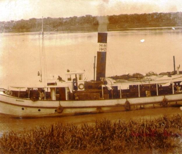 """O navio """"Barbosa"""", pertencente à flotilha da Madeira-Mamoré Railway Co, pertencente ao mega-empresário Percival Farquhar, ancorado em frente aos galpões.  Foto: Dana Merril, 1910"""