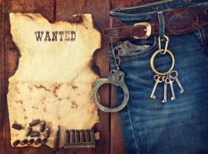 Background in the style of the American West. Handcuffs in jeans.
