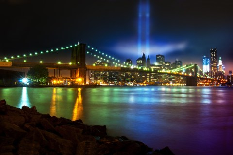 Remembering September 11. NYC Downtown & Brooklyn Bridge viewed from Dumbo. One World Trade Center (Freedom Tower) (under construction) was lit up in patriotic red, white and blue.
