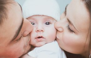mother-and-father-kissing-adorable-little-infant-child