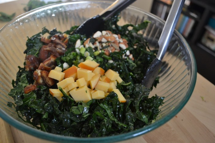 Cheese, nuts and dried fruit top a kale and mint salad