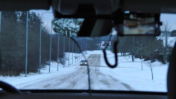 Väntan på fri väg för Labb-Volvons första sladdprovokation på snömodd 2014-12-13. I vindrutans ovankant (till höger om kamerakåpan för City-Safety och Driver Support) sitter tillfälligt en smartphone med app som registrerar g-tal och GPS-deriverad fart samtidigt som vägen filmas.