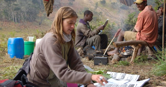 Antje Ahrends prepares herbarium specimens at the forest edge.  (Photo J. Finch)