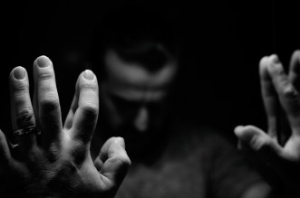 Man in despair with raised hands and bowed head, monochromatic image in a low light room looking in front of mirror