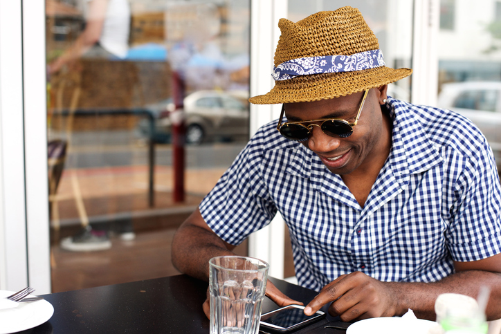 African American man on phone eating outside