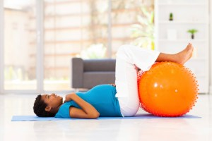 pregnant woman laying on floor with her feet up on a exercise ball