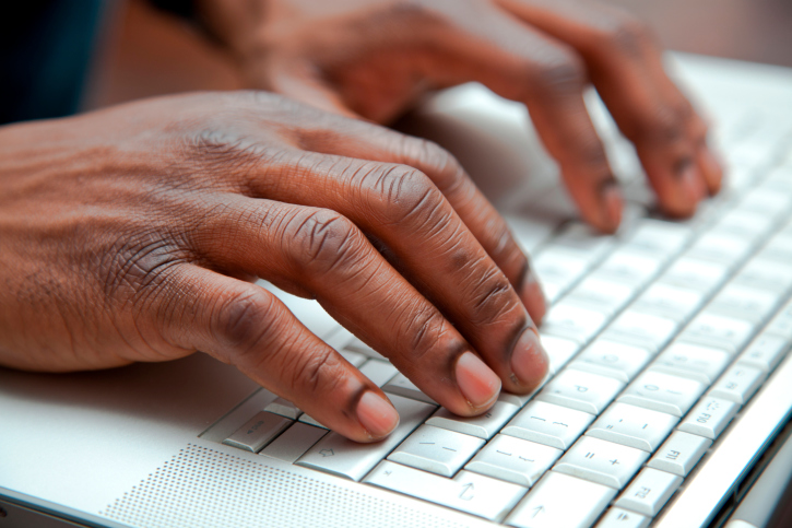 Close up of black hands on a keyboard