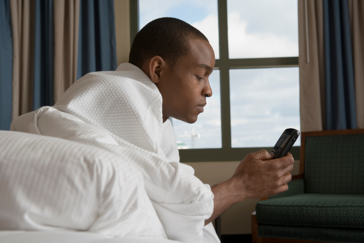 Man lying in bed and checking cell phone