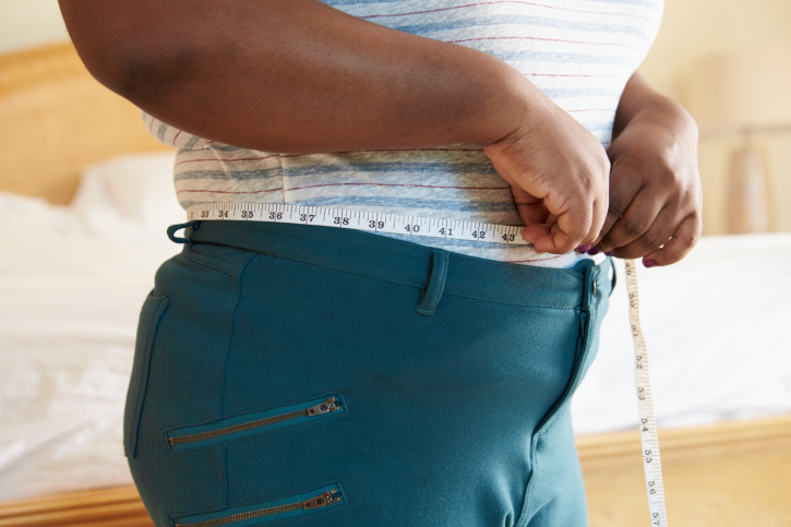 overweight person with a tape measure around waist