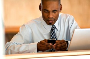 African American Black businessman texting and with laptop