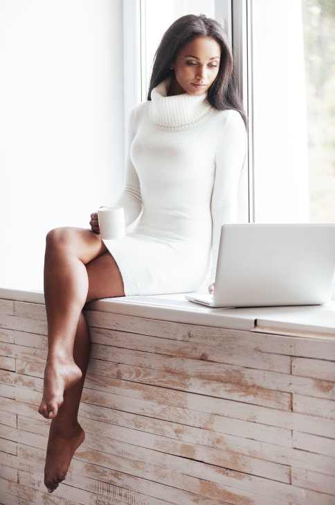 attractive woman sitting in window on laptop