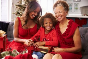 African American Black Girl With Grandmother And Mother Opening Christmas Gifts