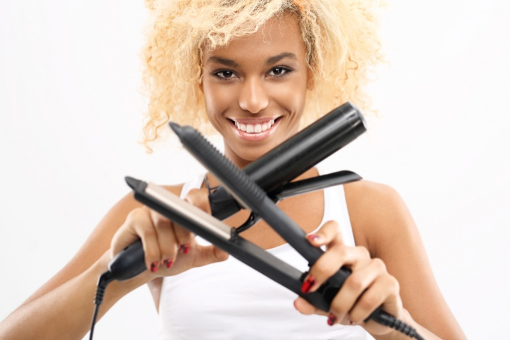 African American woman holding curling iron and flat iron