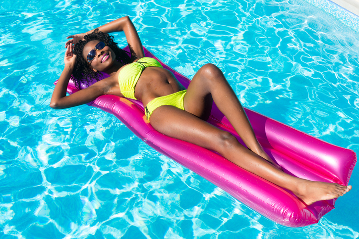 African american woman floating in pool