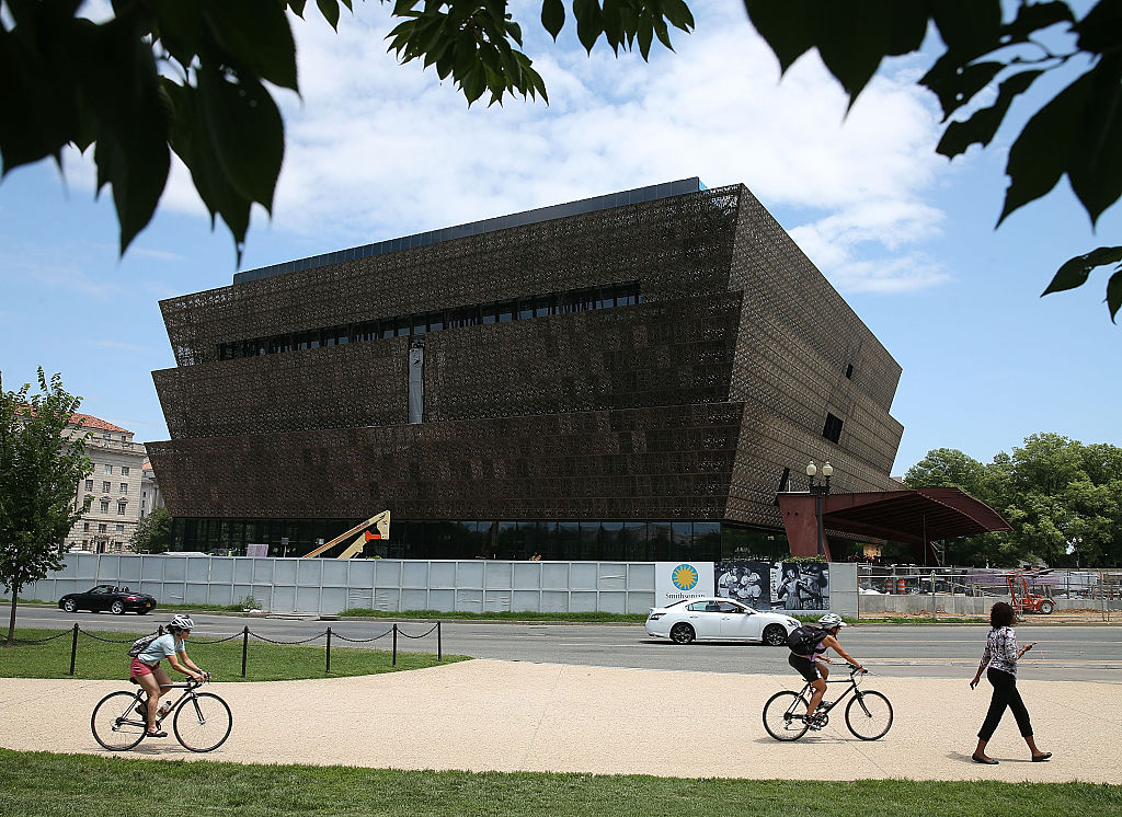 WASHINGTON, DC - JULY 16: Tourist walk past the Smithsonian Museum of African American History and Culture that is currently under construction July 16, 2015 in Washington, DC. The museum is located on the National Mall near the Washington Monument and is scheduled to be completed and dedicated in 2016.Ê