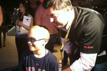 Beckett helps pediatric brain tumor patient William Oulton throw the first ball.
