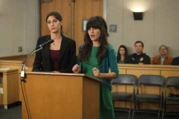 Julia (Lizzy Caplan) reluctantly represents the cutesy Jessica Day (Zooey Deschanel)