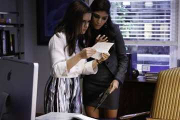 Betsy (Zoe Jarman) and Shauna (Amanda Setton) snoop through Danny's desk as they deal with working Saturdays