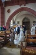 Das Brautpaar zieht in die Kirche ein. Der Hochzeits Fotograf fotografiert das Brautpaar.