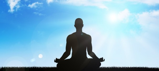 Silhouette of a man figure meditating on sky background