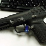 Black Five-seveN USG Pistol leaning against a black keyboard on a gray-to-white background