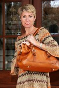 Concealed Carrie founder Leslie Deets models the very popular distressed brown leather satchel, $299. Gun? What gun?