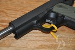 Picture shows a polymer-framed 1911 pistol with od green grips, slide open to expose the barrel.