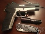 Picture shows a two-toned SIG P226 pistol, a flashlight and knife.