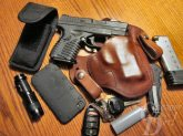Picture shows EDC, a Springfield XD pistol, brown leather holster, a phone, a knife, and a flashlight.
