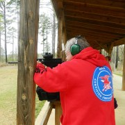 Man wearing red hoodie with NRA logo shooting a rifle