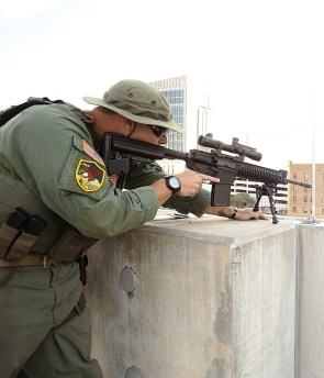 Law enforcement officer shooting from behind a concrete wall using a bipod