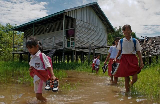 Los estudiantes deben quitarse los zapatos antes de salir de clase durante la temporada de lluvias, cerca del lago Sentarum, Kalimantan Occidental, Indonesia. Una investigación en curso trata de establecer cómo los bosques afectan la sensibilidad de las personas a eventos climáticos tales como inundaciones, así como su capacidad de adaptación para responder a ellos. Fotografía de Ramadian Bachtiar / CIFOR.