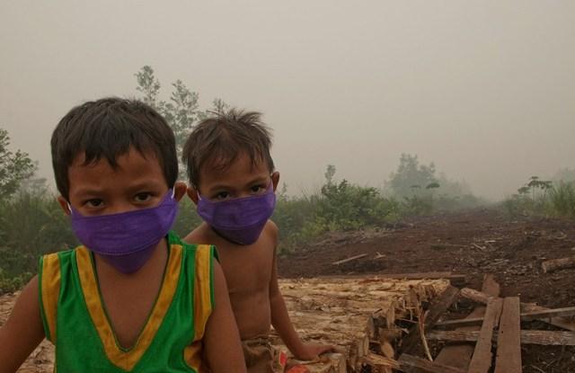 Niños en Palangka Raya, Central Kalimantan usando máscaras contra la densa humareda provocada por los múltiples incendios forestales. Foto Aulia Erlangga/ CIFOR