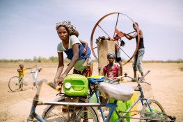 Barry Aliman, 24 years old, bicycles with her baby to fetch water for her family, Sorobouly village near Boromo, Burkina Faso.