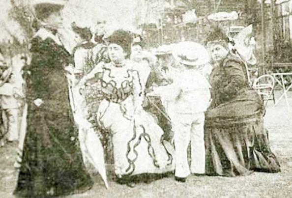Victoria é a de vestido branco e chapéu escuro, no centro da foto.