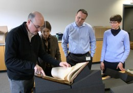 Galbraith and staff members examine a rare book.