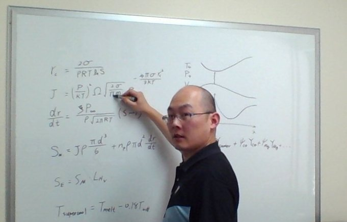 Man standing at a whiteboard covered in mathematical equations