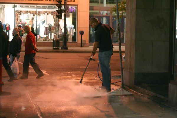 A worker pressure-washes the sidewalk through a Rogers ad template