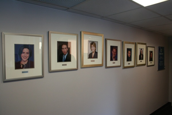 A wall near the entrance shows pictures of the permanent reporting staff