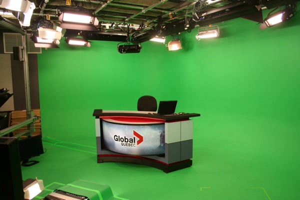 The CKMI studio features an anchor's desk, a chair and a lot of green wall