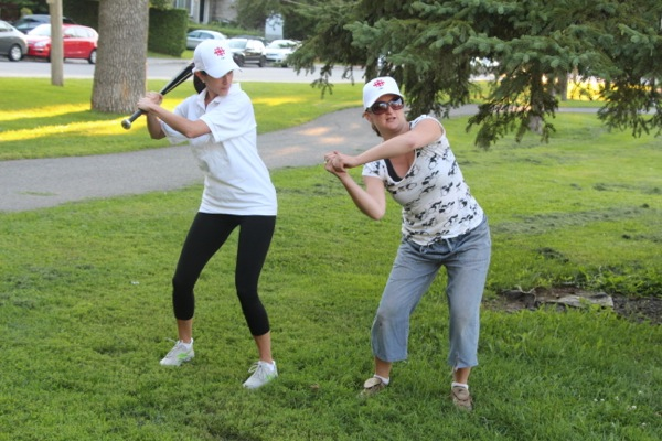 Kristin Falcao gets batting lessons from Corinne Smith.