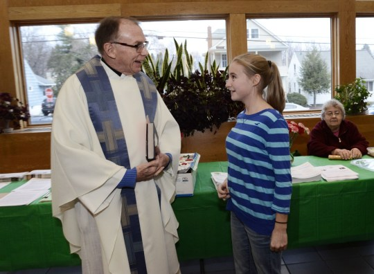 The Rev. Fred Daley greets Grace Moran, 13, before the start of mass at All Saints Church in Syracuse, N.Y., on Dec. 5. Daley came out in 2004.