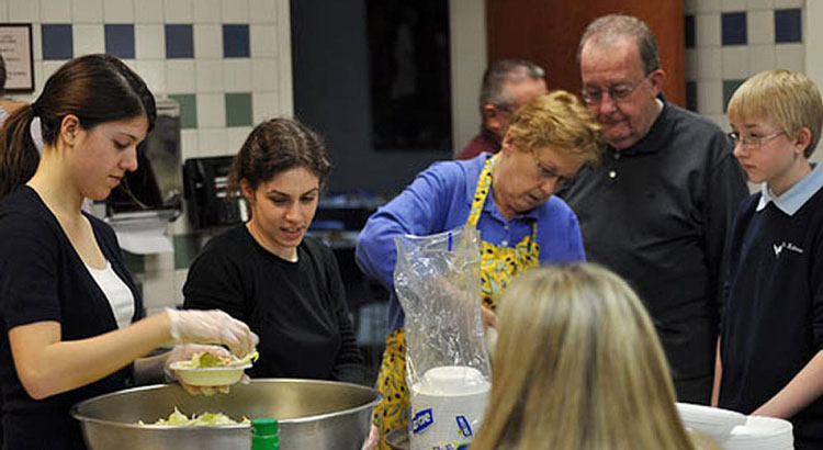 A group of parishioners in gloves and aprons, preparing food for a charitable dinner