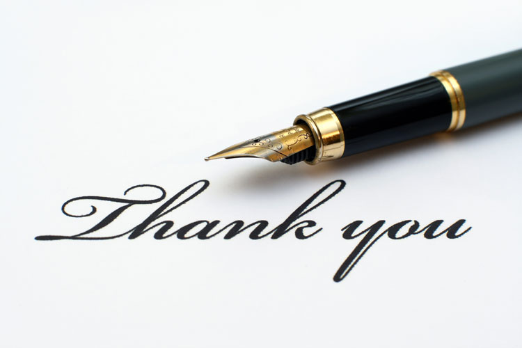 "a fountain pen next to the words ""Thank you"" written in script"