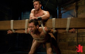 Gay and submissive man is made to carry a big block of wood on him back while naked