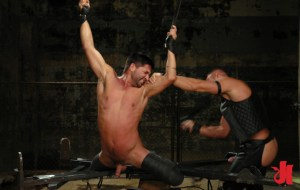 Brunet man, chained to a torture device is flogged while having his arms raised above